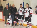 Kinsmen club members presenting the Ice Hawks with new jerseys.